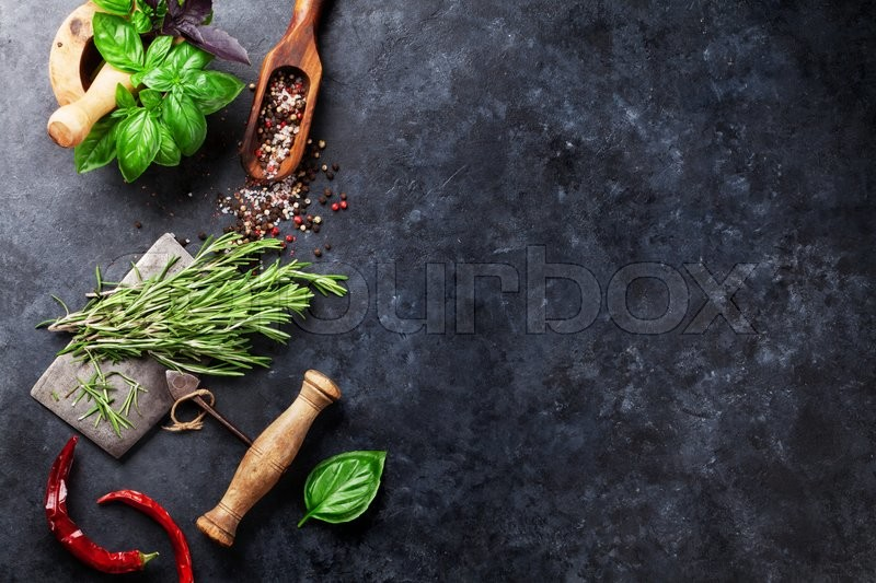 Herbs and spices cooking on stone table. Basil, rosemary, pepper and salt. Top view with copyspace, stock photo