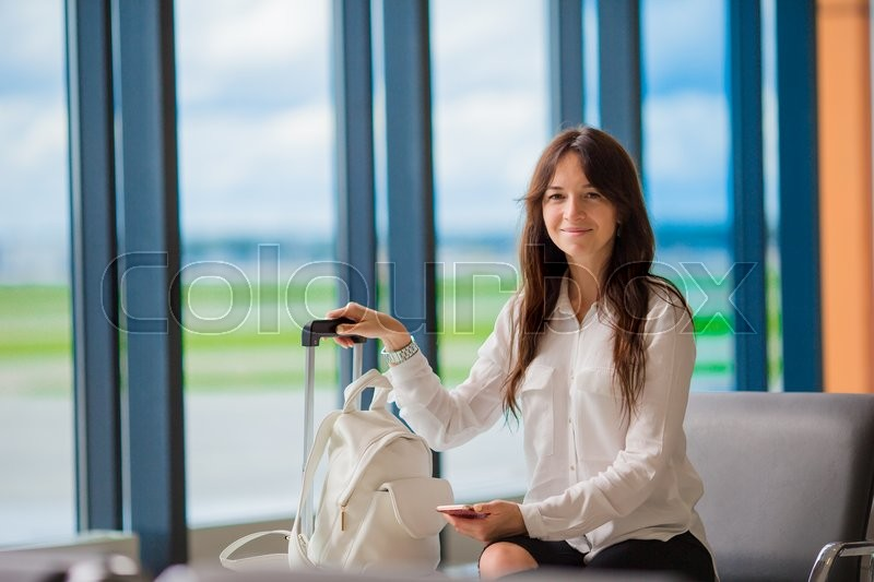 Airline passenger in an airport lounge waiting for flight aircraft. Caucasian woman with smartphone in the waiting room, stock photo