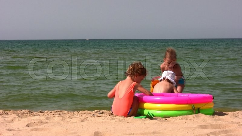 barnet leger ved stranden