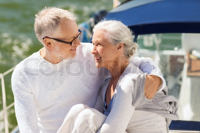 Sailing, age, tourism, travel and people concept - happy senior couple hugging on sail boat or yacht deck floating in sea, stock photo