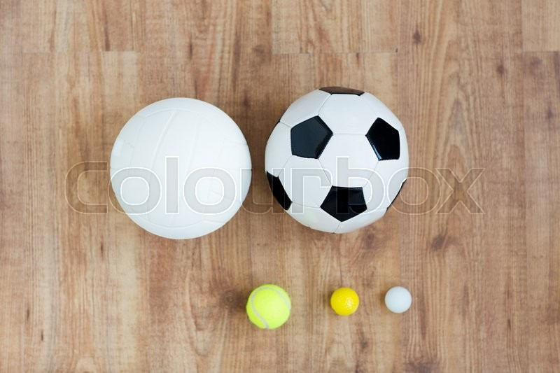 Sport, fitness, game, sports equipment and objects concept - close up of different sports balls set on wooden floor from top, stock photo
