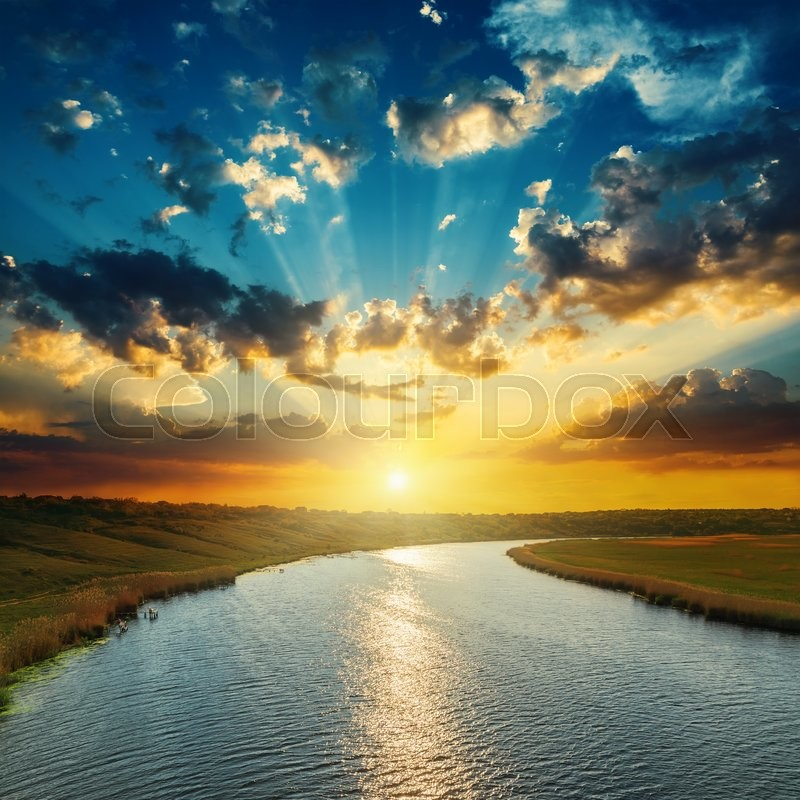 Sunset with clouds, light rays over river with reflections, stock photo