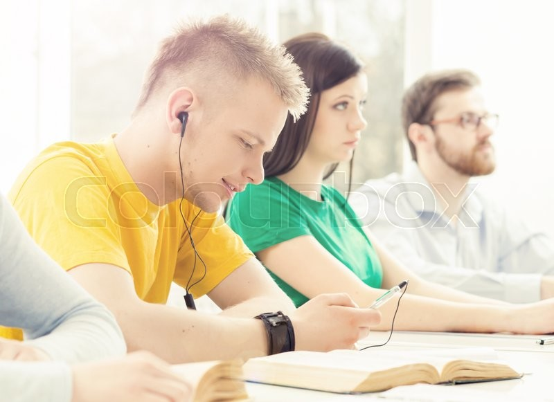 Hipster guy learning to the music in a classroom, stock photo
