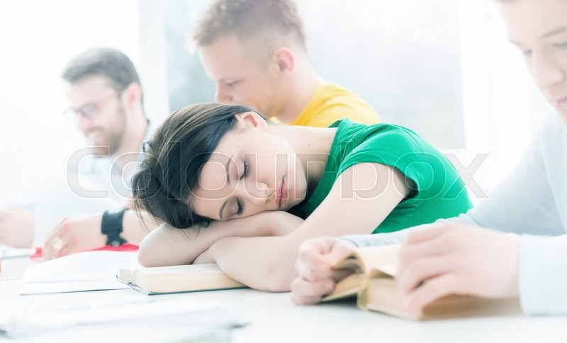 Tired girl sleeping on a lesson. Depression concept, stock photo