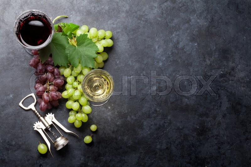 Red and white wine glasses and grape over stone table. Top view with copy space, stock photo