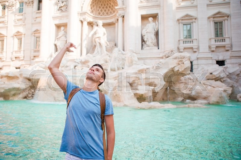Happy man tourist trowing coins at Trevi Fountain, Rome, Italy for good luck. Caucasian guy making a wish to come back, stock photo