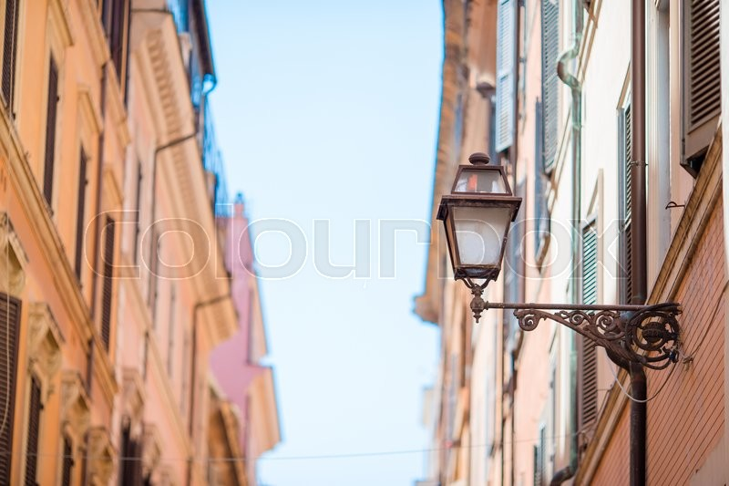 Old beautiful empty streets in Rome, Italy. Close-up of a street light at the town house, stock photo