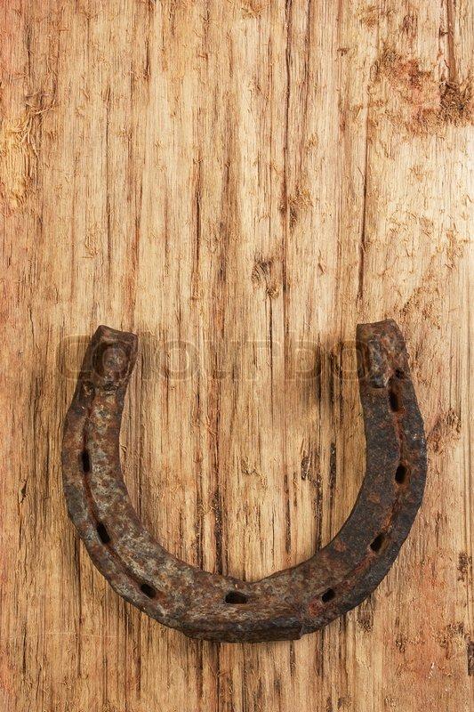 Old Rusty Horseshoe On A Wood Background Stock Photo