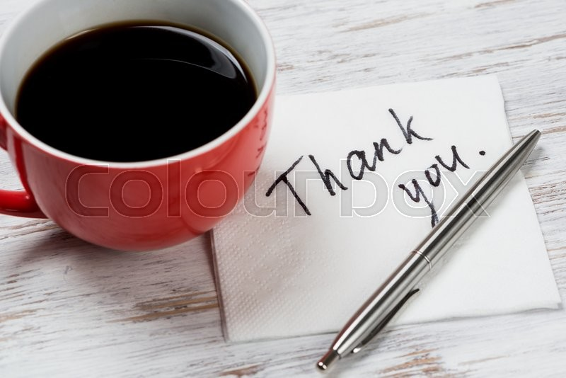 Cup of coffee and napkin with writings on table , stock photo
