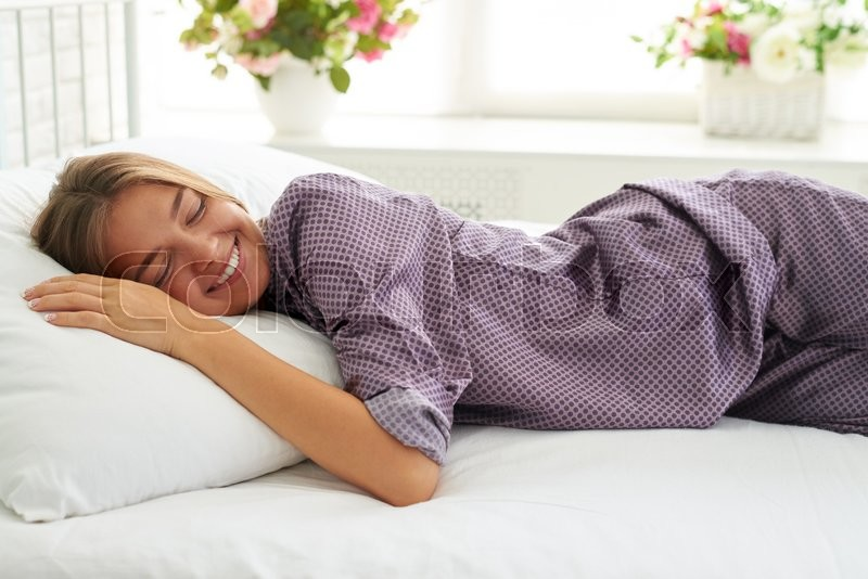 Portrait of smiling beautiful woman lying on the pillow on white bed in light bedroom with closed eyes, stock photo