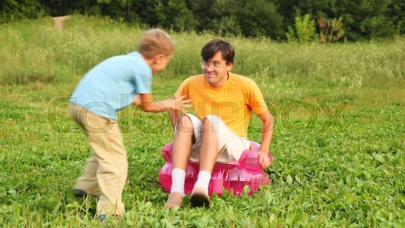 Mann, Junge Und Mädchen Sitzen In Der Kinder  Aufblasbare Sessel Auf Dem  Feld Im Park Und Spielen Den Narren, Stock Video