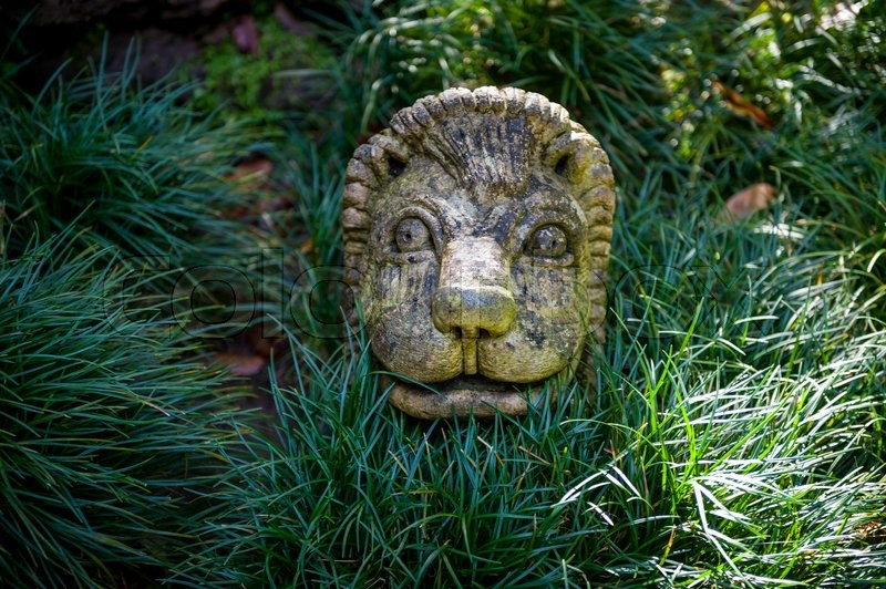 Stone lion face sculpture in the green bushes of Monte park. Funchal, Madeira island, Portugal, stock photo