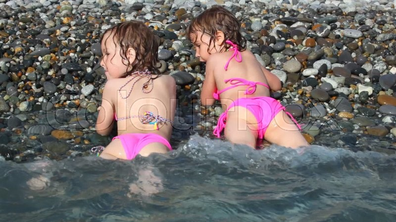 Two happy little girls lying on pebble ... | Stock video | Colourbox