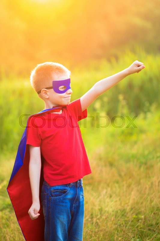 Child playing and portraying super hero and super man outdoors, stock photo