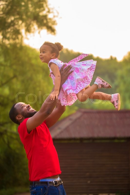 Cute black father and baby girl playing together. Baby flying up in the father\'s hands, stock photo