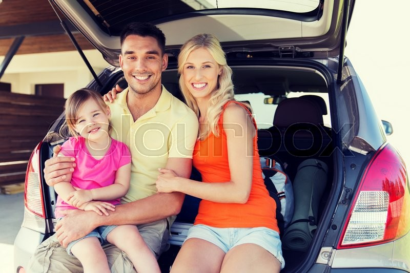 Transport, leisure, road trip and people concept - happy happy family with little girl sitting on trunk of hatchback car at home parking space, stock photo