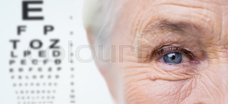 Age, vision, eyesight and people concept - close up of senior woman face and eye over chart background, stock photo