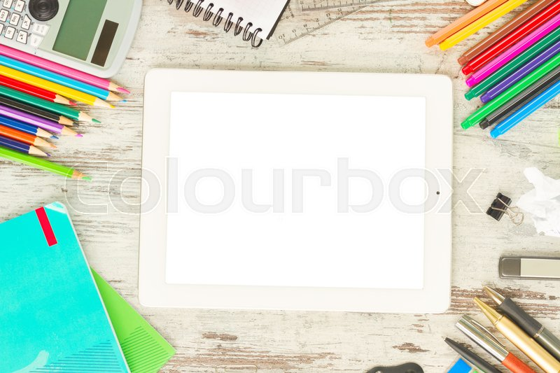 Back to school frame with school supplies and tablet with empty screen on wooden table, stock photo