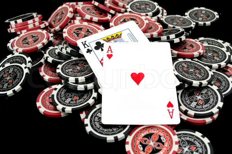 cards and ultimate poker chips on black stock photo