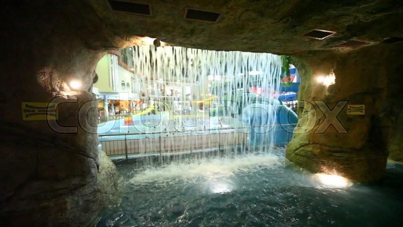 Pool Mit Wasserfall durch einen wasserfall aus stein höhle gesehen badenden personen im