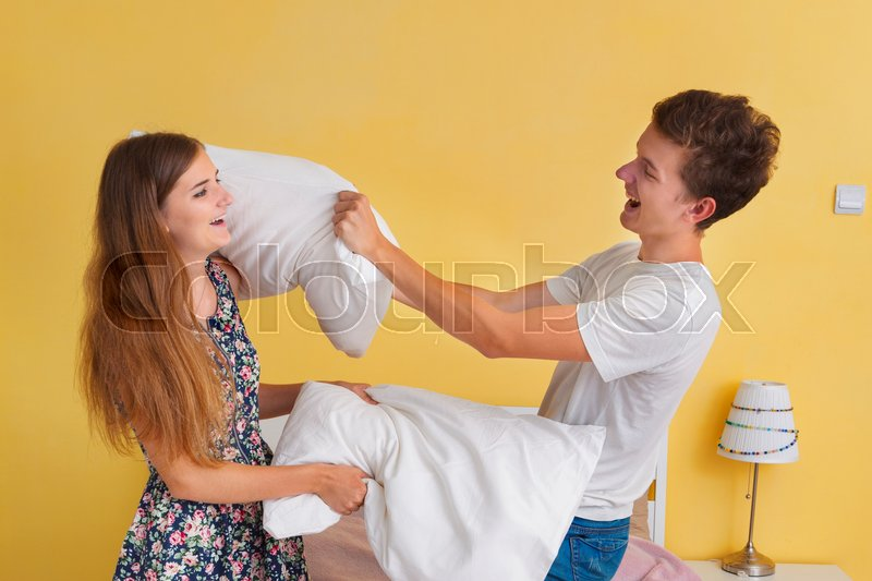 Portrait of young couple teens , pillow fight , stock photo