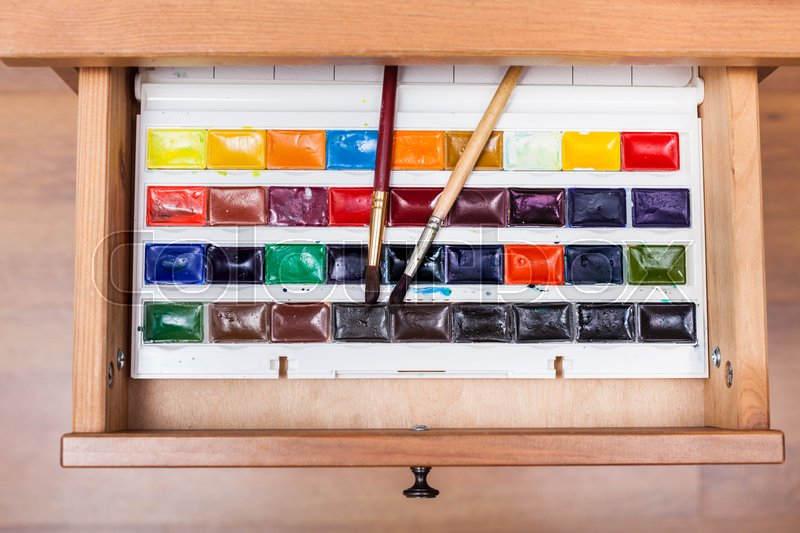 Top view of box with watercolor paints and painting brushes in open drawer of nightstand, stock photo