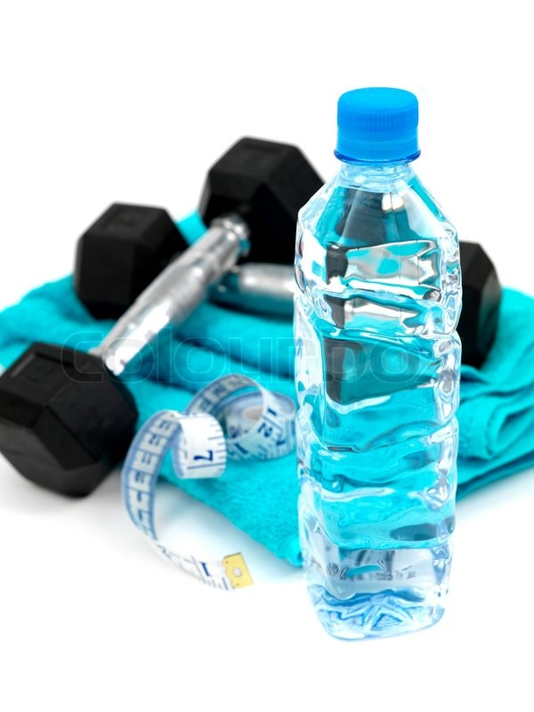A bottle of water and a sports towel and exercise equipment isolated against a white background ...