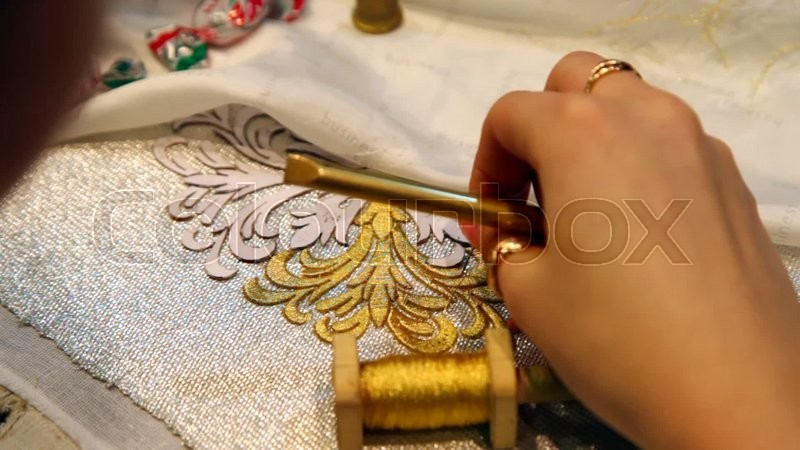 Female hand embroider with gold thread and lace needle on