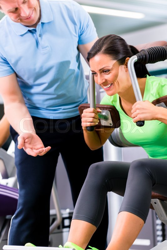 Woman with personal trainer doing sport und fitness in gym, he is showing her the training plan, stock photo