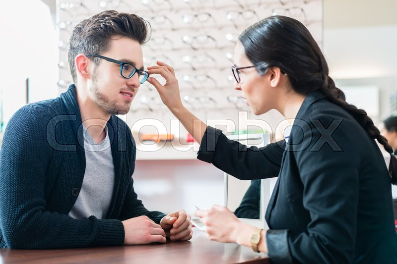 Man in optician shop getting advice from saleswoman buying new glasses, stock photo