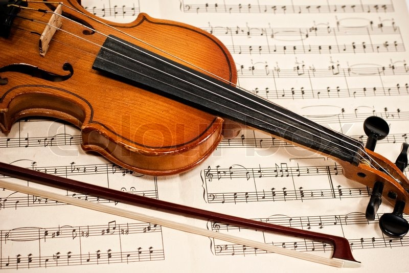 Old violin and bow on musical notes     | Stock image