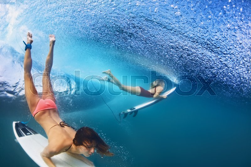 f6e322042a Active girls in bikini in action - surfers with surf board dive underwater  under breaking big ocean wave. Family lifestyle