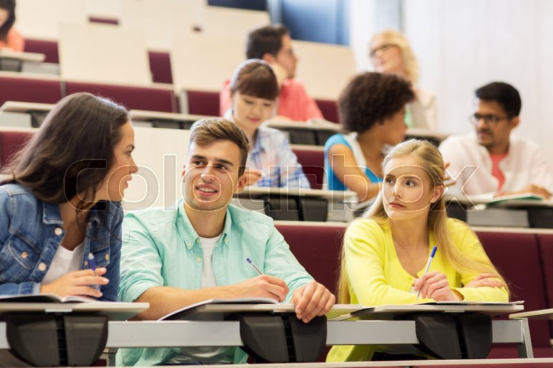 Education, high school, university, learning and people concept - group of international students with notebooks writing in lecture hall, stock photo