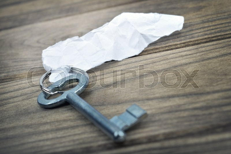 Closeup of key with empty note on wooden table, stock photo