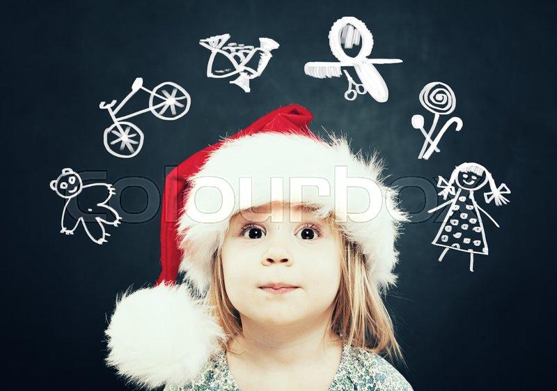 Little Girl in Santa Hat dream on Gifts. Christmas Child , stock photo