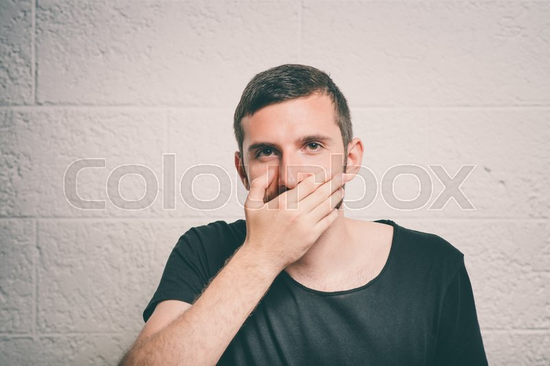 Man laughs and covers her mouth, stock photo