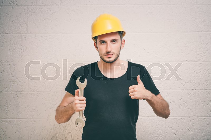 Portrait of young handyman holding a wrench, stock photo