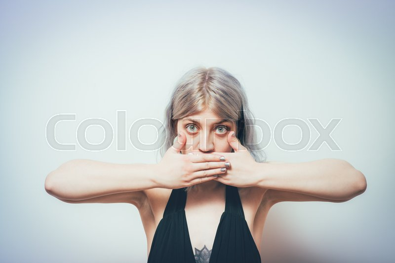 Successful stylish girl covers her mouth with her hands, isolated in the studio, stock photo