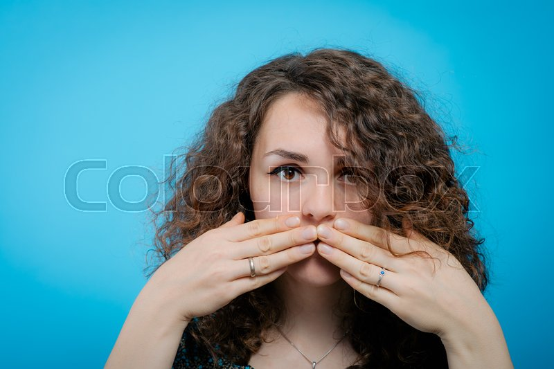 Girl laughs and covers her mouth, stock photo