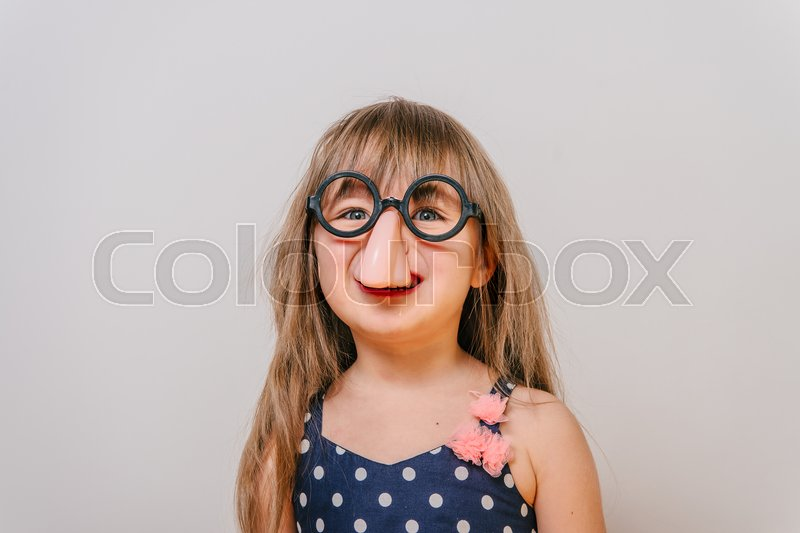 A little girl with glasses. funny glasses humor. little girl laughing. girl clown. Girl looks funny, stock photo