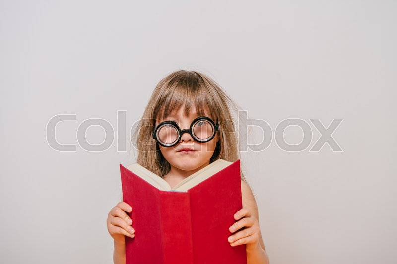 Girl with books. little girl in polka-dot dress. girl with thick book. a little girl with glasses and a book. girl reading. Girl learns. Little Girl tired to learn, stock photo