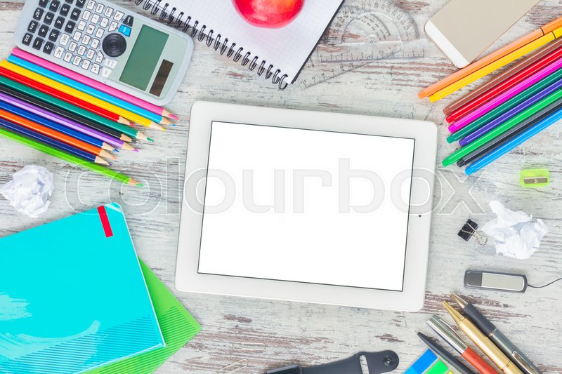 Back to school frame with school supplies, copy space on tablet with empty screen on wooden table, stock photo