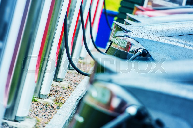 Charging Electric Vehicles Using Public Outdoor Electric Chargers. Modern Electric Cars in Use. Future of Transportation, stock photo