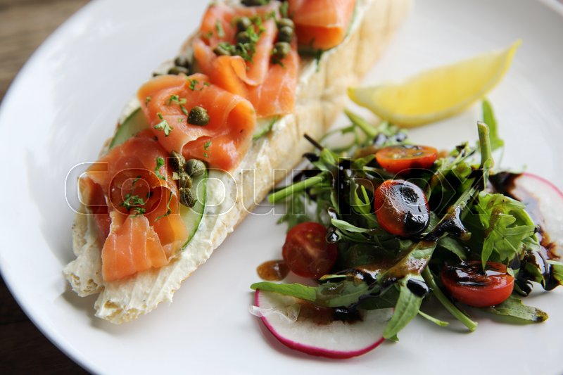 Stock image of 'Smoked salmon on toasted bread with cream fresh, lemon and salad'