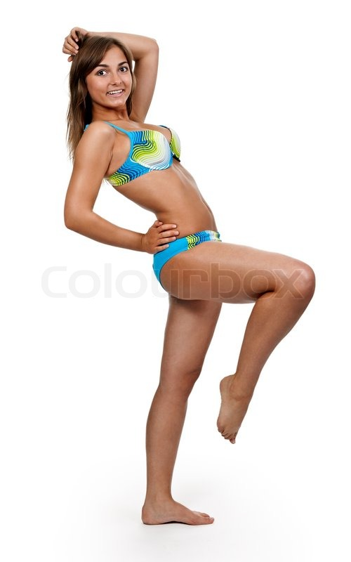 Tanned girl standing on one leg on a white background in a ...