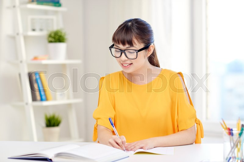 People, education, high school and learning concept - happy asian young woman student in glasses with book and notepad writing at home, stock photo