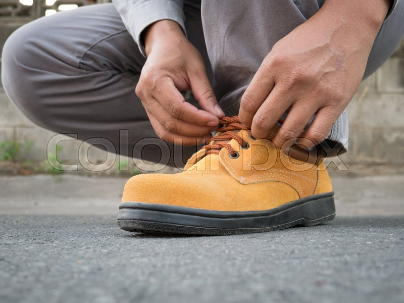 Close up of The man wears safety shoes on street , stock photo