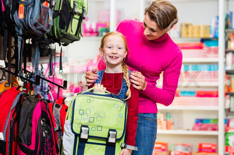Mother and kid becoming a student buying school satchel or bag in store, stock photo
