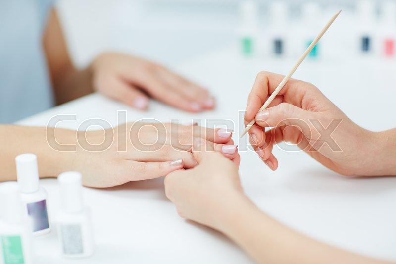 Woman hands receiving a manicure in beauty salon, stock photo