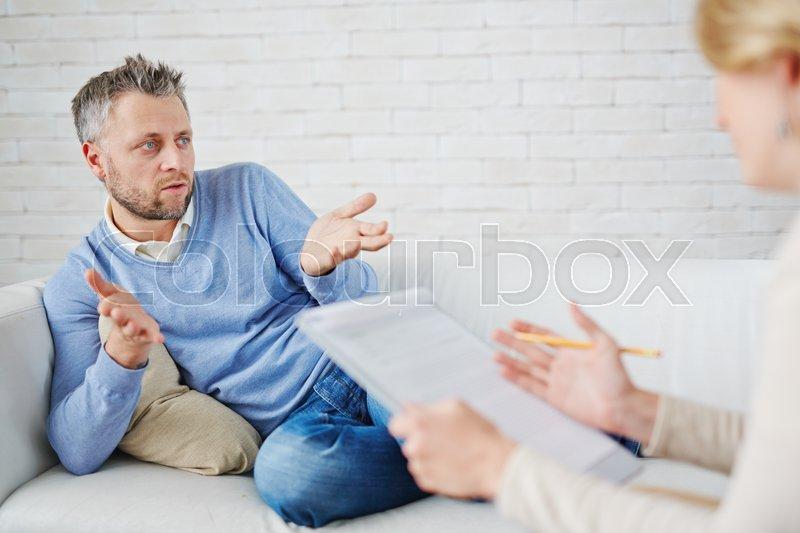 Man describing his problem to psychologist, stock photo